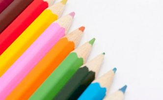 Row of coloured pencil crayons in the colours of the rainbow in a diagonal line with copyspace on a white background